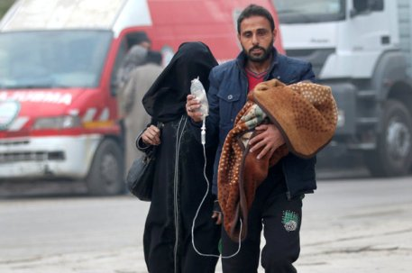 A man carries a child with an IV drip as he flees deeper into the remaining rebel-held areas of Aleppo, Syria December 12, 2016. REUTERS/Abdalrhman Ismail